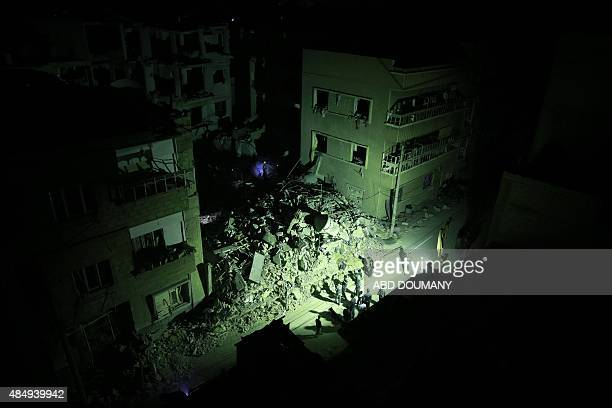 Syrian rescue workers and civilians search for victims under the rubble of collapsed buildings late on August 22 2015 following shelling and air...