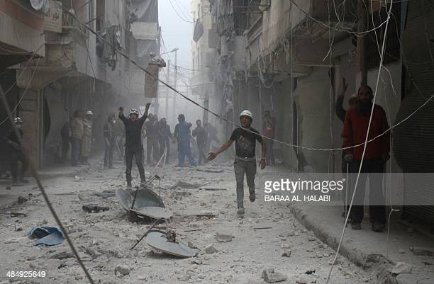 Syrian rescue workers gesture as they stand on a damaged street following reported air strikes by government forces in the Aleppo district of Ansari...