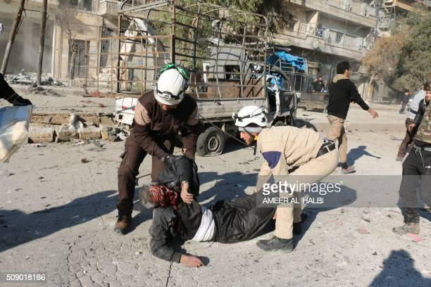 Syrian rescue workers help a badly wounded man following a reported Syrian regime air strike in a rebelcontrolled area in the northern city of Aleppo...