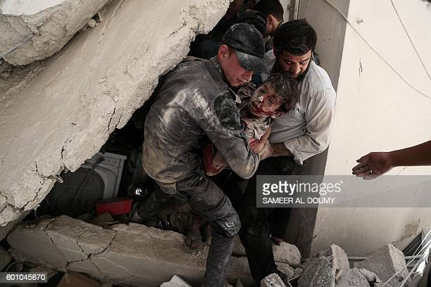 Syrian rescue workers pull a wounded boy from the rubble of a building following reported air strikes on the rebelheld town of Douma east of the...