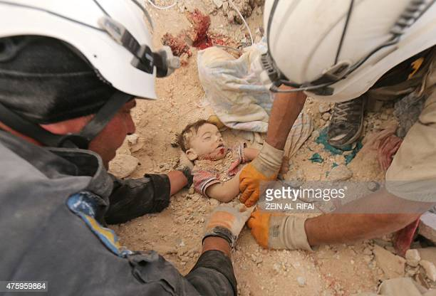 Syrian rescue workers remove the body of a baby from the rubble of a house following a reported bomb barrel attack by Syrian government forces in the...