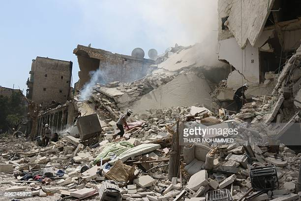 Syrian rescue workers search for victims through the rubble of a building destroyed during a reported barrel bomb attack in a rebelheld neighbourhood...