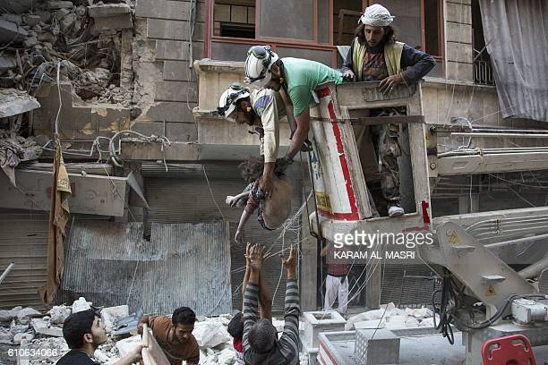 TOPSHOT Syrian rescuers hand the body of a girl down to civilians on the ground after she was pulled from rubble of a budling following government...