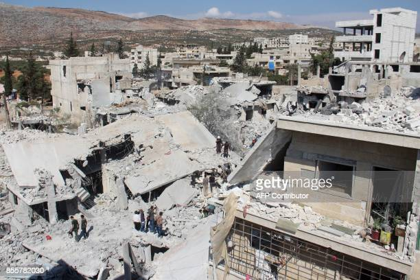Syrian residents and members of the Syrian Civil Defence also known as White Helmets search for victims amid the rubble of buildings following a...