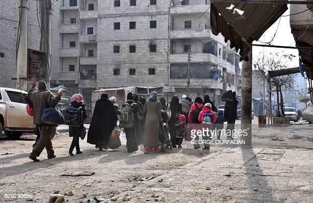 Syrian residents flee violence in Aleppo's eastern alSalihin neighbourhood on December 12 2016 after regime troops retook the area from rebel...