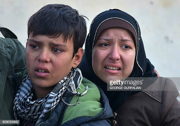 TOPSHOT Syrian residents fleeing the violence in the eastern rebelheld parts of Aleppo react as they evacuate from their neighbourhoods through the...