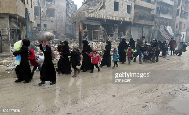TOPSHOT Syrian residents fleeing violence in the restive Bustan alQasr neighbourhood arrive in Aleppo's Fardos neighbourhood on December 13 after...