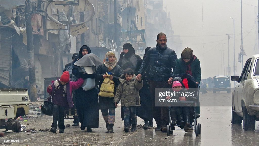 TOPSHOT - Syrian residents, fleeing violence in the restive Bustan al-Qasr neighbourhood, arrive in Aleppo's Fardos neighbourhood on December 13, 2016, after regime troops retook the area from rebe...
