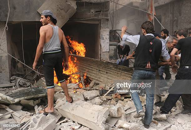 Syrian residents inspect the damaged area after warcrafts belonging to the Syrian army bombed residential areas in Ein Tarma district in Damascus...
