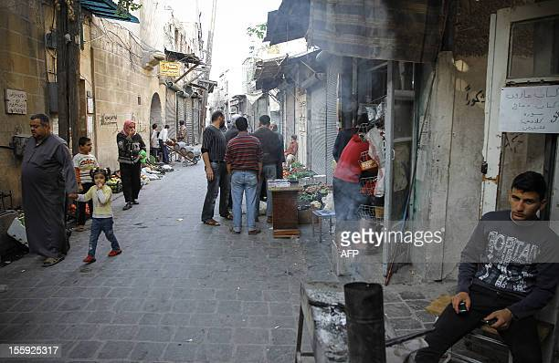 Syrian residents of Aleppo's Bab alNusra district the ancient heart of the city try to return to normal life as fighting between rebels and regime...