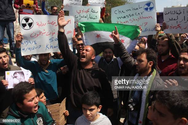 Syrian residents of Khan Sheikhun hold placards and pictures on April 7 2017 during a protest condemning a suspected chemical weapons attack on their...