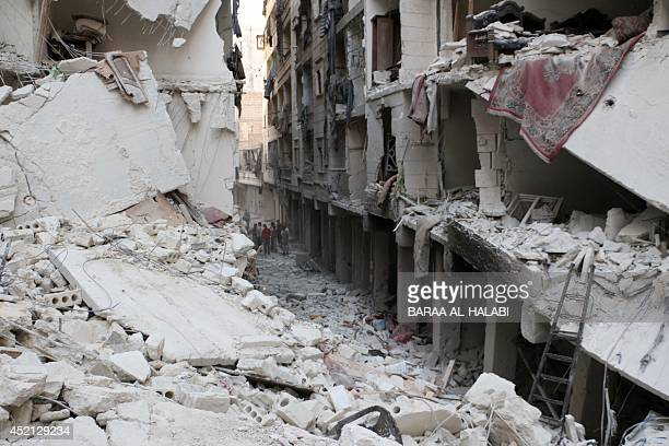 Syrian residents stand amid the rubble of destroyed buildings on July 14 2014 after a reported overnight air strike by government forces in the...