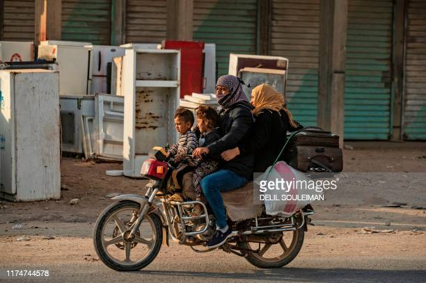 Syrian ride a motorcycle as Arab and Kurdish civilians amid Turkish bombardment on Syria's northeastern town of Ras alAin in the Hasakeh province...