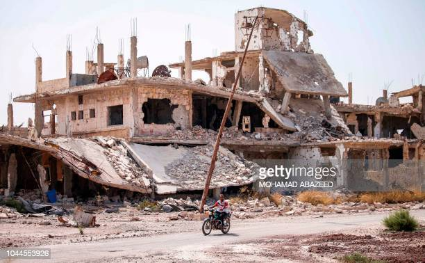 Syrian rides a motorcycle past destroyed buildings in an opposition-held neighbourhood of the southern city of Daraa on October 2, 2018.