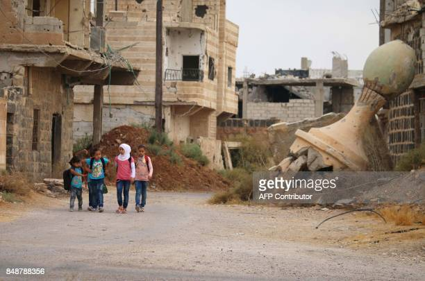Syrian schoolchildren walk past destroyed buildings in a rebelheld area of the southern city of Daraa on September 17 2017 / AFP PHOTO / Mohamad...