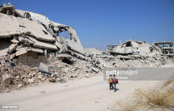 TOPSHOT Syrian schoolchildren walk past destroyed buildings in a rebelheld area of the southern city of Daraa on September 17 2017 / AFP PHOTO /...