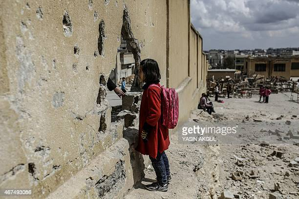 Syrian schoolgirl stands next a damaged wall outside her school in the Syrian Kurdish town of Kobane, also known as Ain al-Arab, on March 25, 2015....
