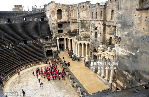 TOPSHOT Syrian scouts tour the Roman Theatre at Bosra a World Heritage Site south of Sweida in the Daraa province on November 23 2018