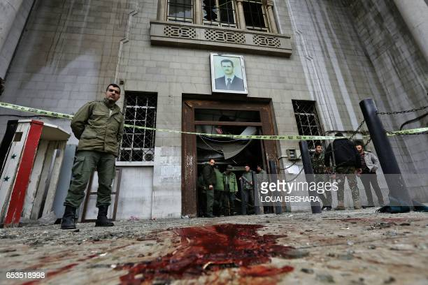Syrian security forces gather under a portrait of President Bashar alAssad at the old palace of justice building in Damascus following a reported...
