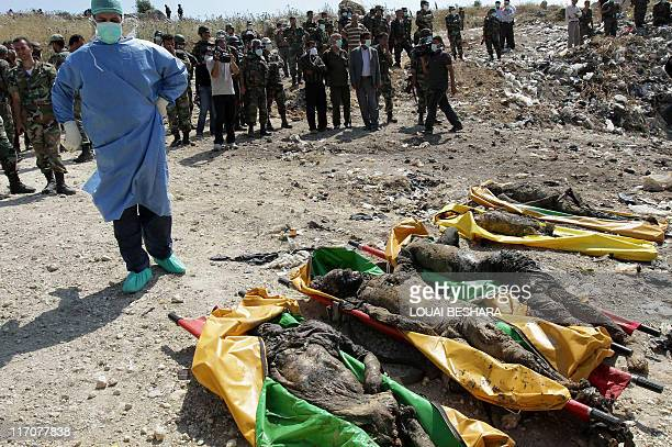 Syrian security forces stand guard near bodies which the government said were found at a mass grave under a pile of rubbish in Jisr alShughur 325 kms...