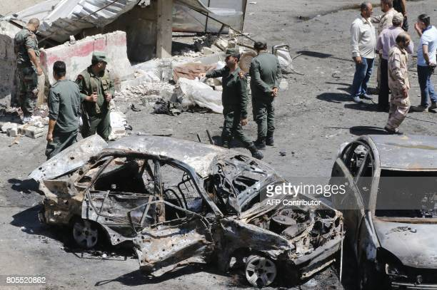 Syrian security members stand next to charred vehicles as they inspect the damage at the site of a suicide bomb attack in the capital Damascus'...