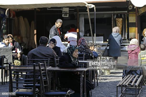 Syrian sits at a cafe at the Hamidiyeh popular market in the old part of the capital Damascus on November 27 2016 / AFP / LOUAI BESHARA