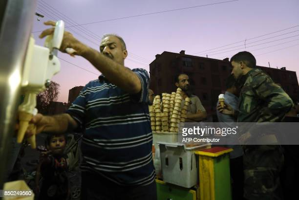 A Syrian soldier and civilians buy ice cream in the eastern city of Deir Ezzor on September 20 2017 as Syrian government forces continue to press...