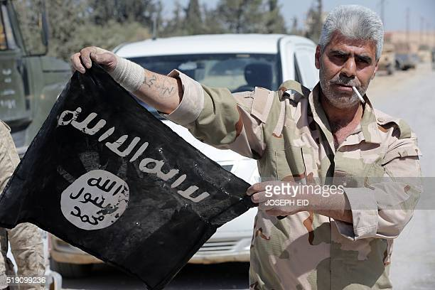 A Syrian soldier displays on April 4 2016 an Islamic State group flag after Syrian troops regained control the previous day of alQaryatain a town in...