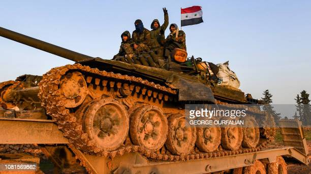 Syrian soldier flashes the victory gestures as he sits with comrades atop a tank being transported near the northern town of Manbij on January 12...