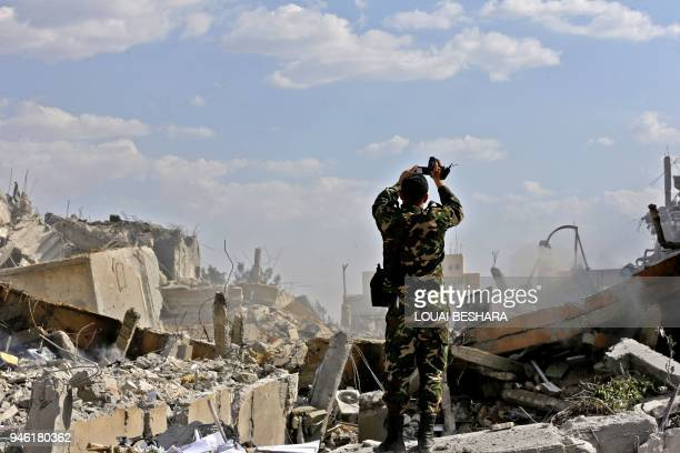 Syrian soldier inspects the wreckage of a building described as part of the Scientific Studies and Research Centre compound in the Barzeh district...