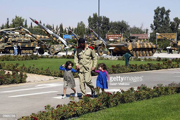 Syrian soldier leads two children through an exhibition about the 1973 ArabIsraaeli war at the '6 October Museum' on October 6 2003 in Damascus Syria...