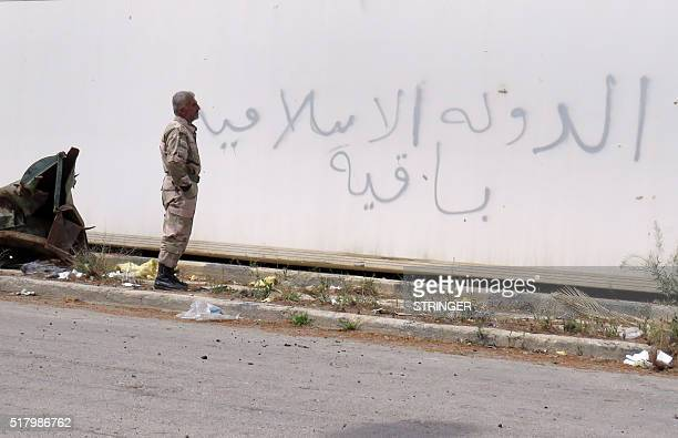 A Syrian soldier looks at graffiti reading in Arabic 'The Islamic State is staying' in the historical city of Palmyra in central Syria on March 29...