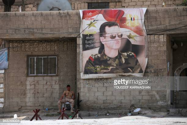 Syrian soldier sits next to a poster of the Syrian president at the entrance of the Wafideen Camp as they wait for the arrival of buses carrying...