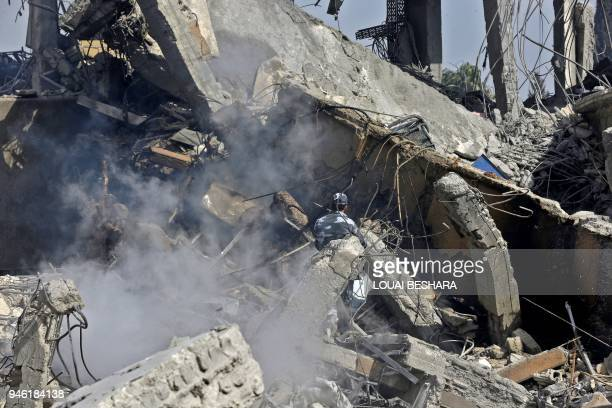 A Syrian soldier sprays water on the wreckage of a building described as part of the Scientific Studies and Research Centre compound in the Barzeh...