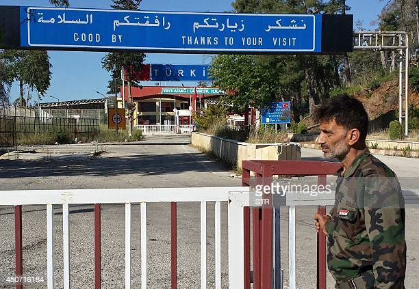 A Syrian soldier stands at a SyrianTurkish border crossing near the town of Kasab in the Latakia province on June 16 2014 Syria's army said it had...