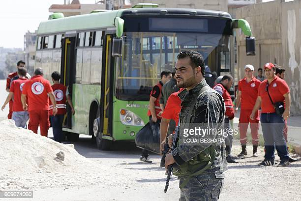 Syrian soldier stands guard as Red Crescent members wait for opposition fighters and their families to change buses at a Syrian army checkpoint on...