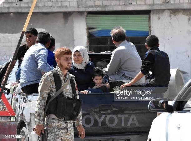 A Syrian soldier stands guard as Syrians ride in a vehicle at the Abu Duhur crossing on the eastern edge of Idlib province on August 20 2018...