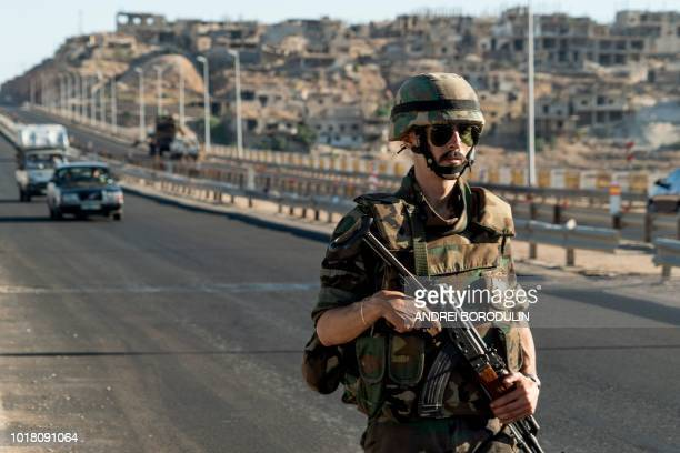 A Syrian soldier stands guard on a main road leading to the town of Rastan in the central Homs province on August 15 2018 Syria's government forces...