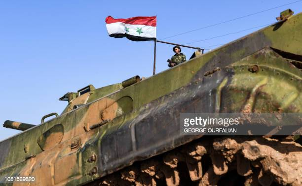 Syrian soldier stands in a government forces' position near a deployed infantryfighting vehicle in the village of Hawshariya northeast of the...