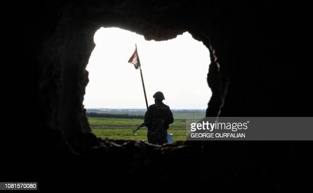 Syrian soldier stands near a Syrian flag flying at a government forces' position in the village of Jubb Makhzoum northwest of the northern town of...