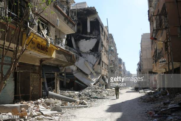 Syrian soldier takes photos in the town of Harasta in Eastern Ghouta on March 26 after government forces entered the town and struck an evacuation...