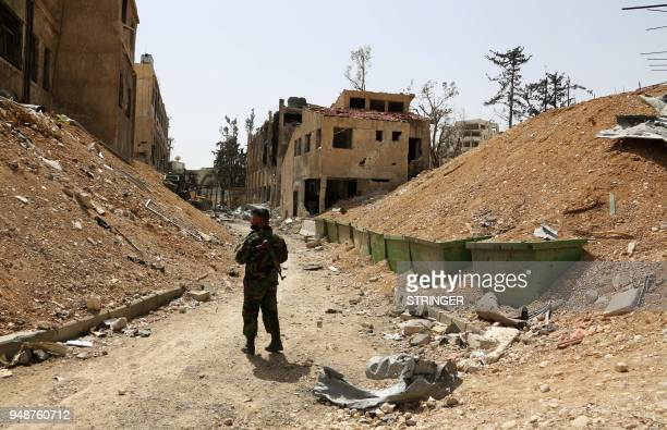 A Syrian soldier walks down a destroyed street in the former rebelheld Syrian town of Douma on the outskirts of Damascus on April 19 five days after...