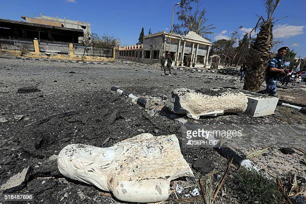 A Syrian soldier walks past the remains of a statue in a heavily damaged street in a residential neighbourhood in the adjacent modern town to the...