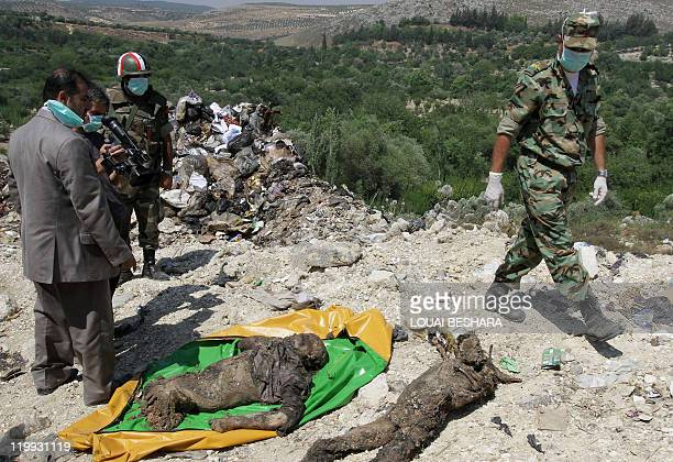 Syrian soldiers and a cameraman gather around human remains which the government said were found at a mass grave in Jisr alShughur 325 kms northwest...