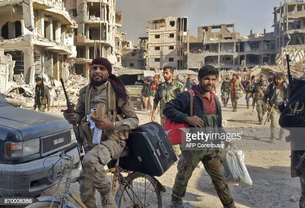 Syrian soldiers and progovernment forces are seen in front of damaged buildings in the eastern Syrian city of Deir Ezzor on November 3 2017 The...