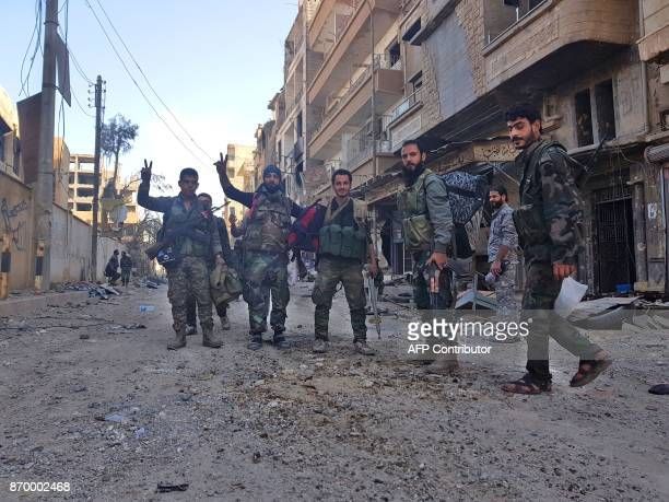 Syrian soldiers and progovernment forces pose for a picture in front of damaged buildings in the eastern Syrian city of Deir Ezzor on November 3 2017...