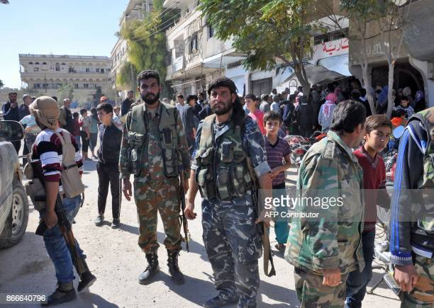 Syrian soldiers and proregime militiamen gather as civilins queue up behind them to receive supplies in a street in the recently retaken desert town...