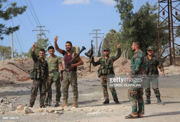 Syrian soldiers gesture on September 4 2016 at a location on the southern outskirts of the Syrian city of Aleppo after regime forces retook control...