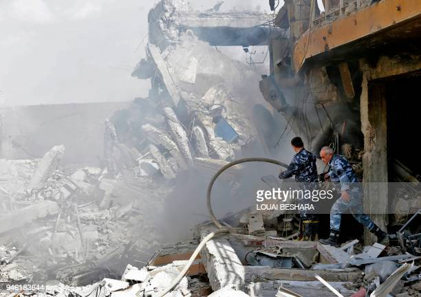 TOPSHOT Syrian soldiers inspect the wreckage of a building described as part of the Scientific Studies and Research Centre compound in the Barzeh...