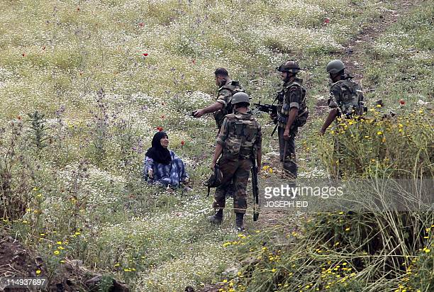 Syrian soldiers prepare to hand over an elderly Syrian woman to Lebanese army troops as she was found trying to cross the border into northern...